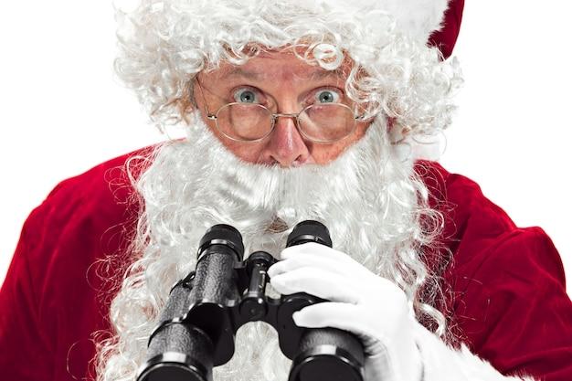 Weihnachtsmann mit einem luxuriösen weißen bart, der weihnachtsmannmütze und einem roten kostüm lokalisiert auf einem weißen hintergrund mit fernglas