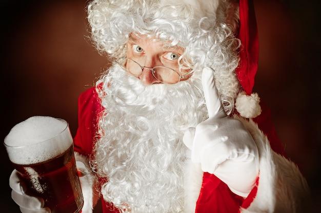 Weihnachtsmann mit einem luxuriösen weißen bart, einer weihnachtsmannmütze und einem roten kostüm