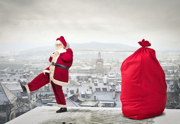 Weihnachtsmann mit einer großen packung auf einem dach