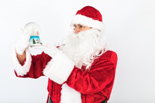Weihnachtsmann mit einer weihnachtsschneekugel in ihren händen, auf weißem hintergrund