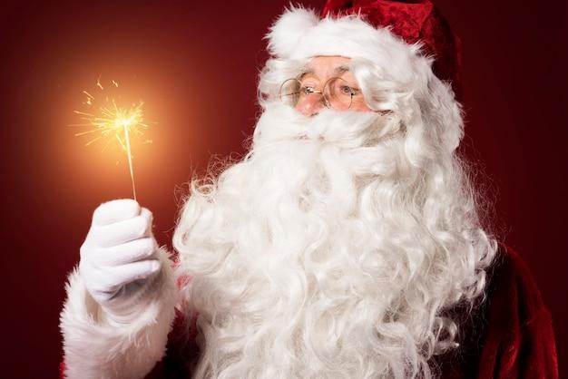 Weihnachtsmann mit einer wunderkerze auf rotem hintergrund