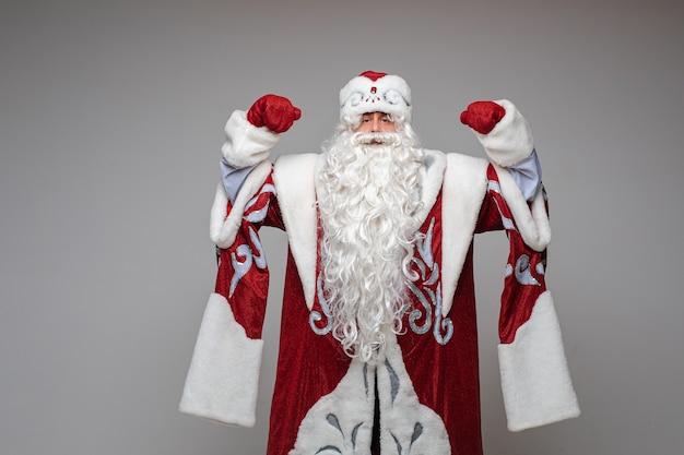 Weihnachtsmann mit erhobenen händen im roten kostüm