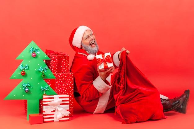 Weihnachtsmann mit festlicher stimmung, geschenkkarton aus der tasche nehmen, kamera betrachten und lächeln.