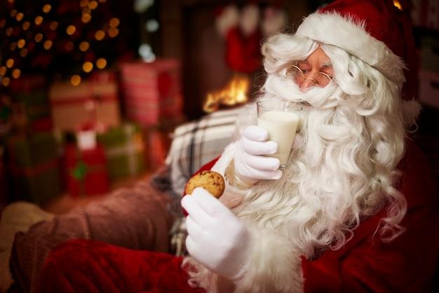 Weihnachtsmann mit glas milch und süßem keks