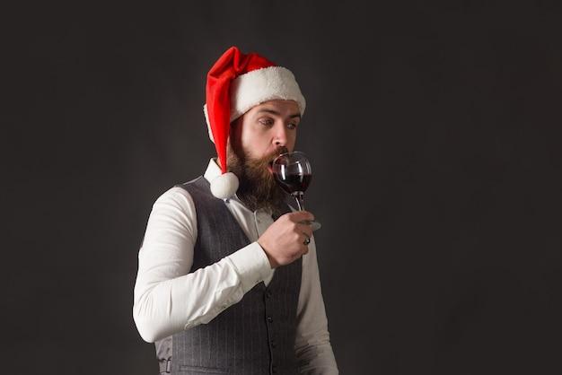 Weihnachtsmann mit glas wein rotwein mann in weihnachtsmütze mit glas wein mann im anzug trinkt wein