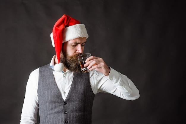 Weihnachtsmann mit glas wein. rotwein. weihnachtsmann mit glas wein. mann im hut des neuen jahres trinkt wein. alkohol. mann mit bordeaux. verkostung von alkohol.