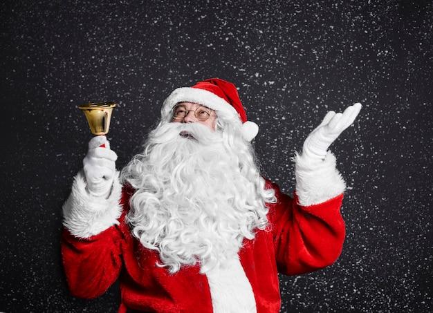 Weihnachtsmann mit handglocke unter schneefall