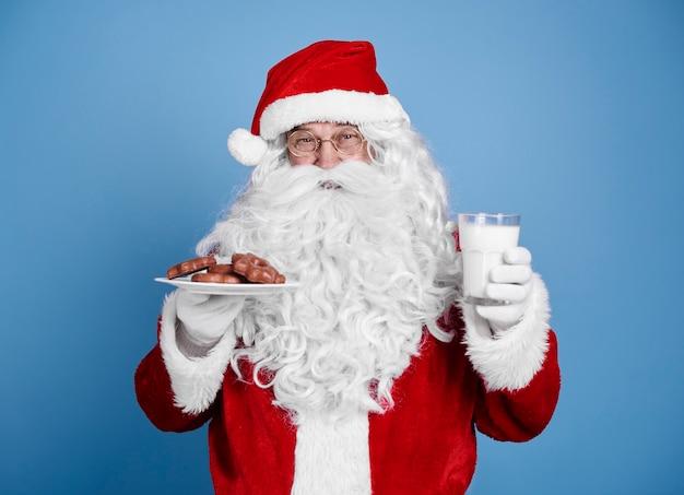 Weihnachtsmann mit keks und milch bei studioaufnahme