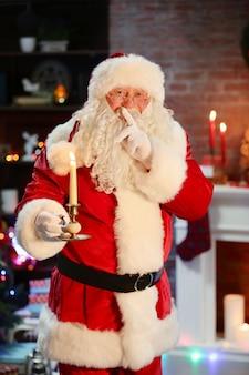 Weihnachtsmann mit kerze weihnachtsinnenhintergrund