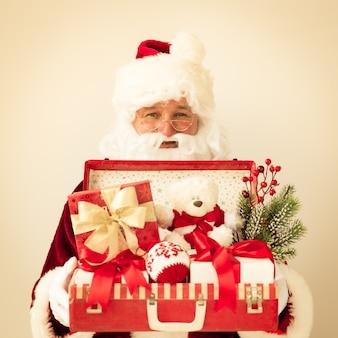 Weihnachtsmann mit koffer. weihnachtsferienkonzept