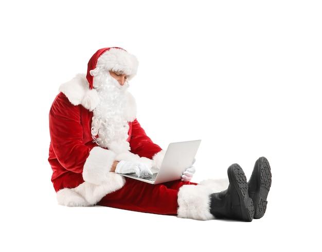 Weihnachtsmann mit laptop, der e-mails auf weißem hintergrund überprüft