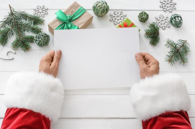 Weihnachtsmann mit leerem brief am tisch