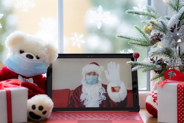Weihnachtsmann mit medizinischer maske seniorenbegrüßung im videochat