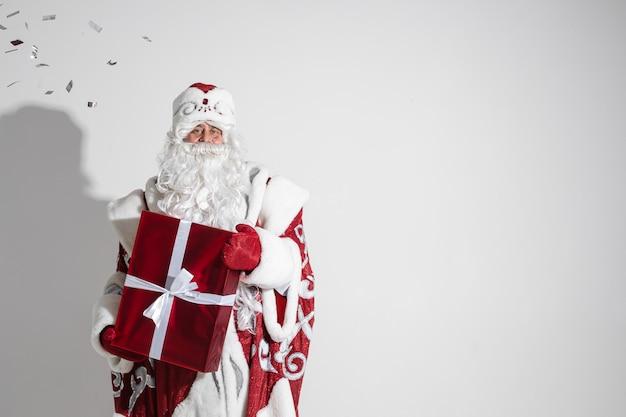 Weihnachtsmann mit rotem weihnachtsgeschenk, das im studio aufwirft