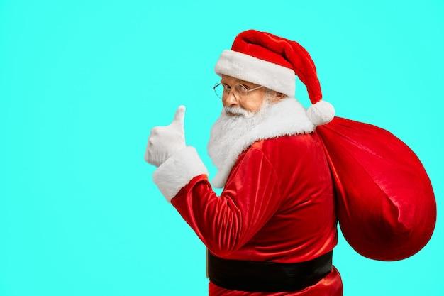 Weihnachtsmann mit tasche, die daumen oben zeigt.