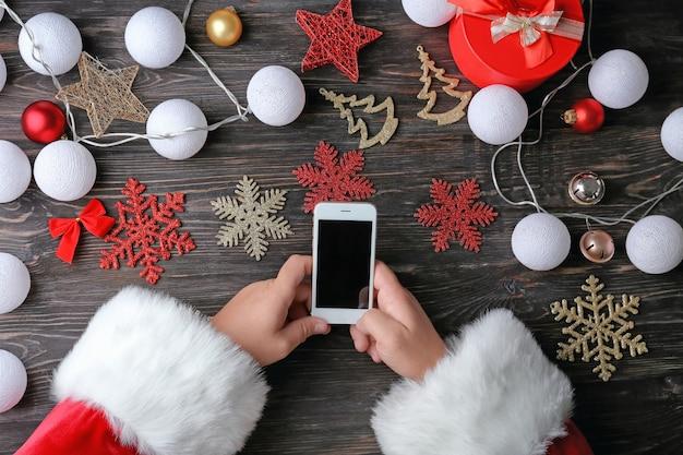 Weihnachtsmann mit telefon am holztisch