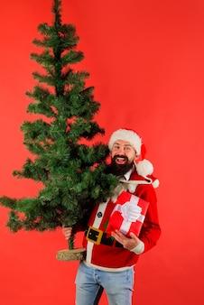 Weihnachtsmann mit weihnachtsbaum neujahr konzept dezember bärtiger weihnachtsmann mann im weihnachtskostüm