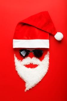 Weihnachtsmann mütze und bart aus schnee mit schwarzer brille