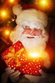Weihnachtsmann öffnet geschenkbox. weihnachtsferienkonzept. weihnachtsgeschenk Premium Fotos