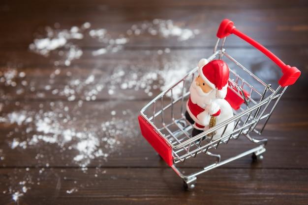 Weihnachtsmann-puppe auf einkaufswagen