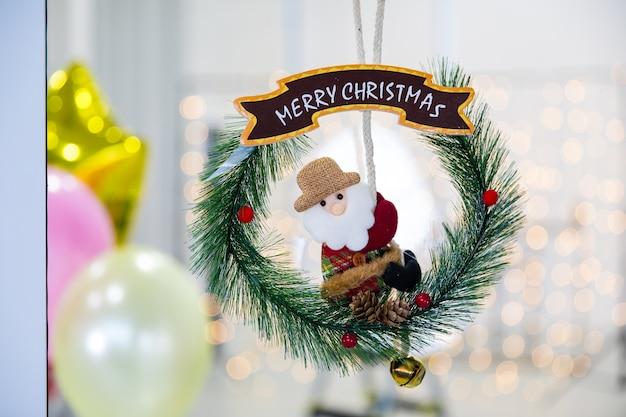 Weihnachtsmann-puppe auf mobilem weihnachtskranz des kreises mit lichter-bokeh-unschärfe im hintergrund.