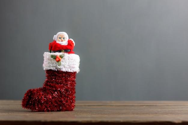 Weihnachtsmann-puppenstand in den festlichen verzierungen der roten socke frohe weihnachten concept.blur grauer hintergrund mit kopienraumbereich. wesentliche einzelteile u. zeichendekorationen auf modernem rustikalem hölzernem schreibtisch des holzes zu hause.
