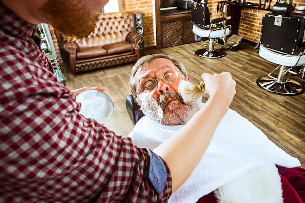 Weihnachtsmann rasiert seinen persönlichen friseur