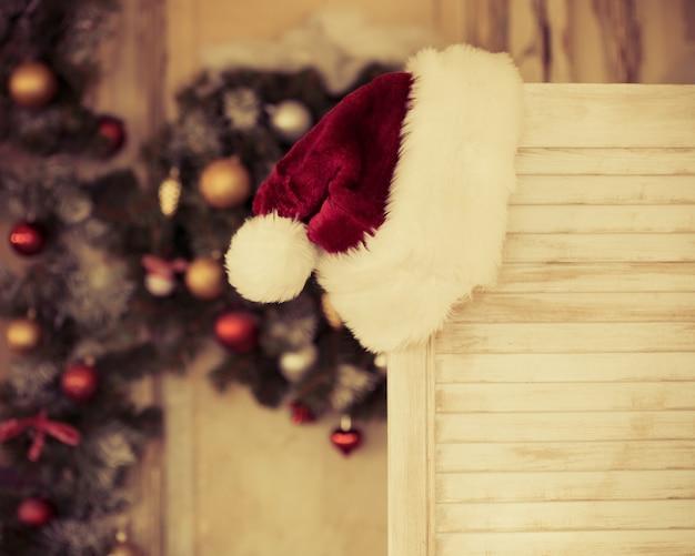Weihnachtsmann-roter hut gegen weihnachtsbaum. weihnachtsferienkonzept