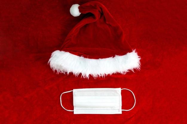 Weihnachtsmann roter hut mit medizinischer gesichtsmaske auf weihnachtsmann-anzug stoff, covid-19 und weihnachtskonzept, hintergrundtexturschönheit