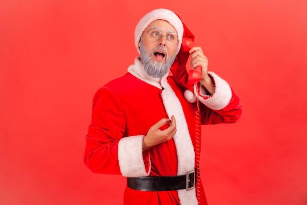 Weihnachtsmann ruft an, hält festnetztelefonhörer und gratuliert zum winterurlaub.