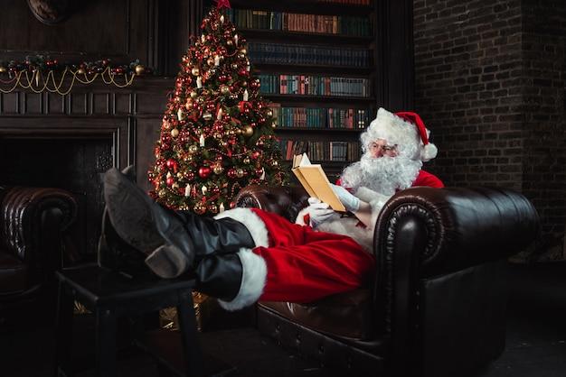 Weihnachtsmann ruht im sofa und liest ein buch