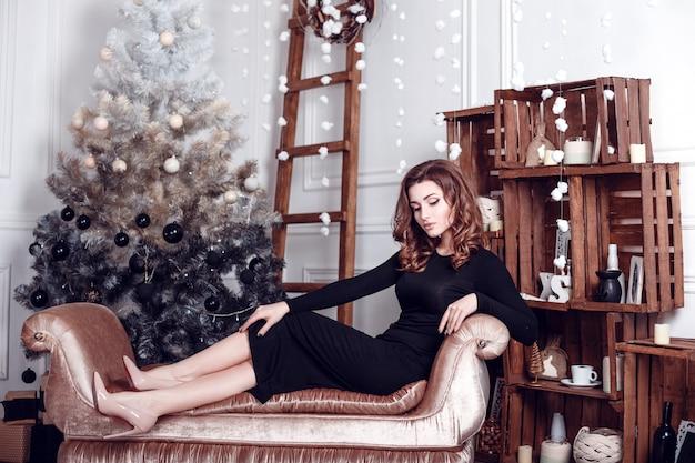 Weihnachtsmann. schönes lächelndes frauenmodell. bilden. gesunde lange frisur. elegante dame im schwarzen kleid über weihnachtsbaum beleuchtet hintergrund. frohes neues jahr