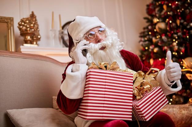 Weihnachtsmann sitzt auf der couch und spricht am handy nahe dem kamin und dem weihnachtsbaum mit geschenken. frohe weihnachten, frohe feiertagskonzept
