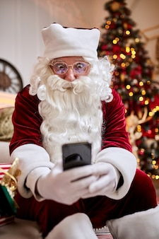 Weihnachtsmann sitzt auf der couch und spricht am handy nahe dem kamin und dem weihnachtsbaum mit geschenken.