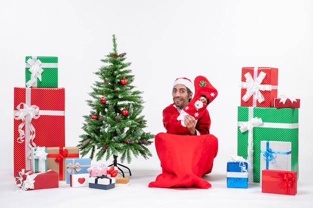 Weihnachtsmann sitzt mit geschenkboxen und baum