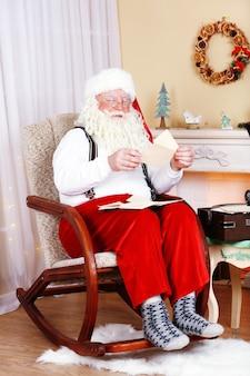 Weihnachtsmann sitzt mit kinderbriefen im bequemen stuhl in der nähe des kamins zu hause