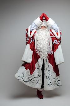 Weihnachtsmann steht auf einem fuß in baumhaltung.