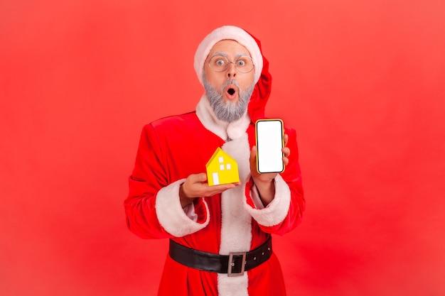 Weihnachtsmann steht mit papierhaus und handy mit leerem bildschirm, umzugsdienste