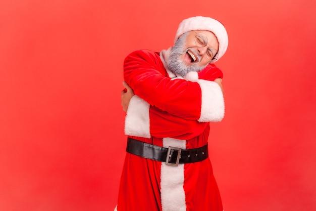 Weihnachtsmann umarmt sich, fühlt sich wohl, narzisstische egoistische person, glücklicher ausdruck.