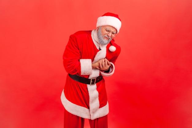 Weihnachtsmann umklammert die brust und verzieht das gesicht wegen schmerzhafter krämpfe, herzinfarkt in jungen jahren