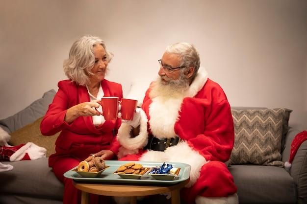 Weihnachtsmann und ältere frau feiern