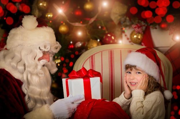 Weihnachtsmann und glückliches kind. kinder träumen. weihnachtsferienkonzept. weihnachtsgeschenk Premium Fotos