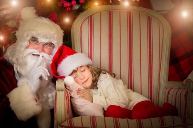 Weihnachtsmann und glückliches kind. kinder träumen. weihnachtsferienkonzept. weihnachtswunder