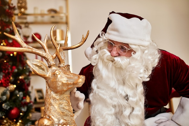 Weihnachtsmann und hirsch in der nähe des kamins und des weihnachtsbaumes mit geschenken.