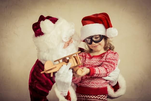 Weihnachtsmann und kind spielen mit vintage-holzflugzeug zu hause weihnachtsgeschenk-feiertagskonzept