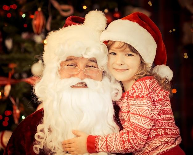 Weihnachtsmann und kind zu hause gegen weihnachtsbaum. konzept für den familienurlaub.