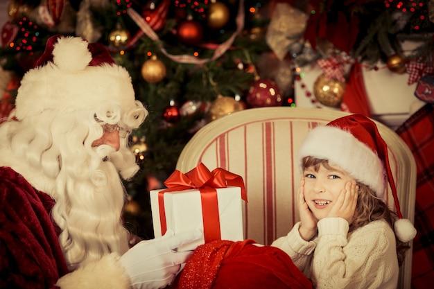 Weihnachtsmann und kind zu hause. weihnachtsgeschenk. familienurlaubskonzept Premium Fotos