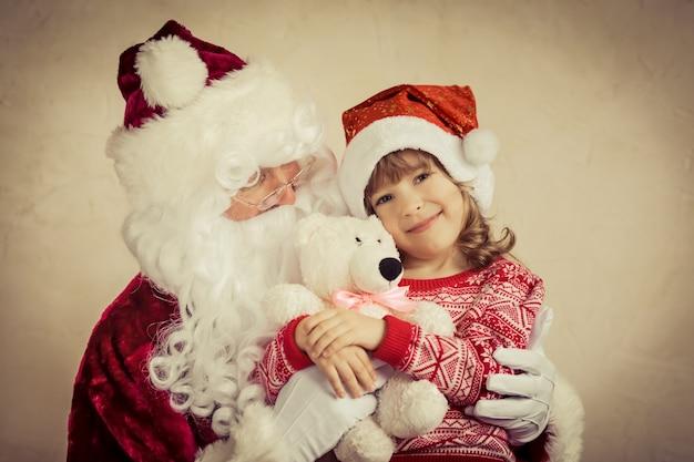 Weihnachtsmann und kind zu hause. weihnachtsgeschenk. familienurlaubskonzept