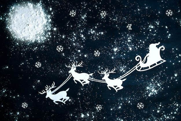 Weihnachtsmann und rentier fliegen durch den nachthimmel. weihnachtshintergrund.