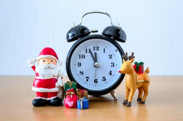 Weihnachtsmann und uhr, hirsch und geschenk auf tisch. frohes neues jahr und weihnachtskonzept